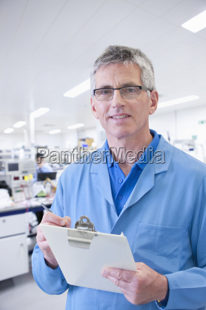 male engineer with clipboard in electronics