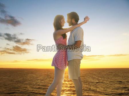 romantic couple embrace as sun sets