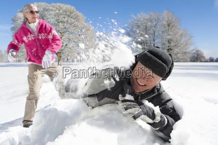 romantic mature couple having snowball fight