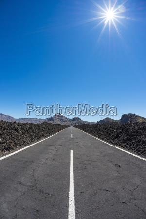 road through lava field with sun