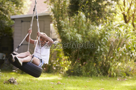 young girl playing on tire swing