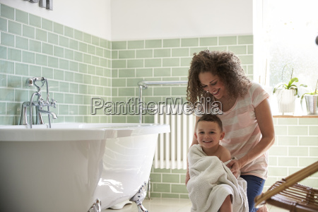 mother drying son with towel after