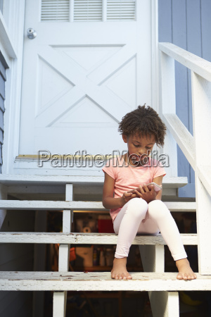young girl sits on outdoor steps