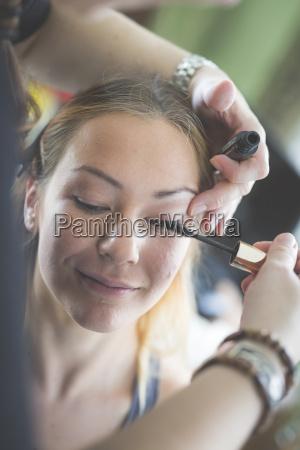 stylist applying mascara on womans eyelashes