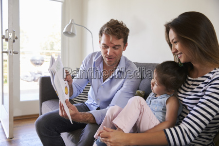 parents reading with baby daughter on