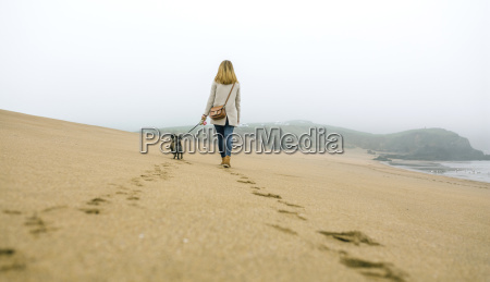 woman, walking, with, dog, on, the - 20525967