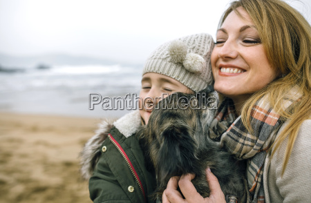 mother and daughter hugging their dog