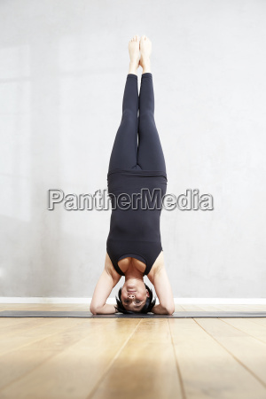 woman practising yoga doing a headstand