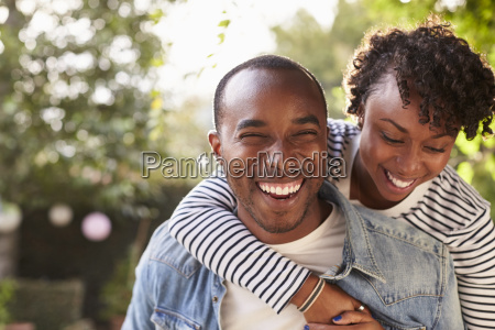 laughing young black couple piggyback in