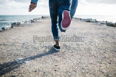 legs of young man running on