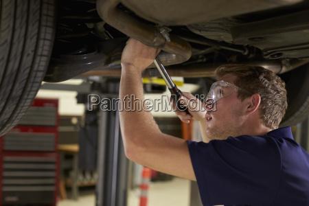 auto mechanic working underneath car in