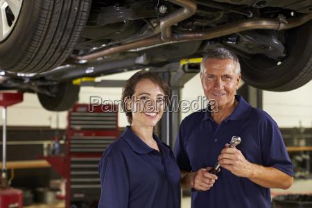 male and female mechanics working underneath