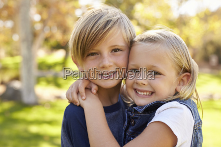 young brother and sister embracing in