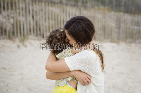 happy mother hugging little daughter on