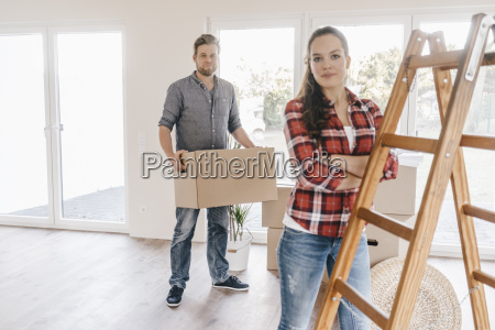 couple moving house carrying boxes in