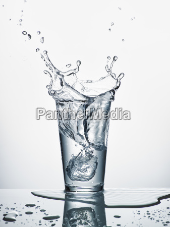 glass with sinking ice cube and