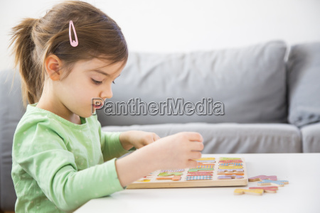 little girl learning alphabet with wooden