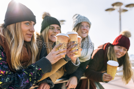 four friends toasting with coffee to