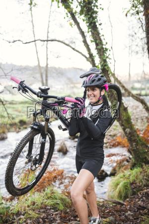 smiling woman carrying her mountain bike