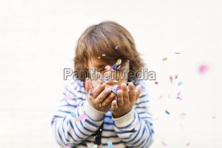 boy blowing colorful confetti from there