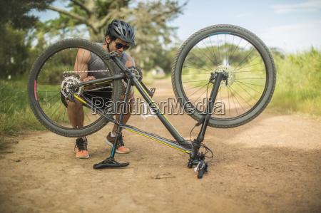 young man fixing mountain bike on
