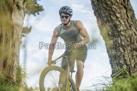young man mountain biking in nature