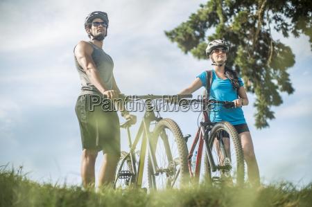 young couple mountain biking in nature