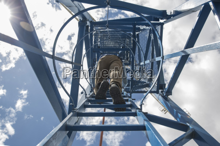 worker climbing on construction crane view