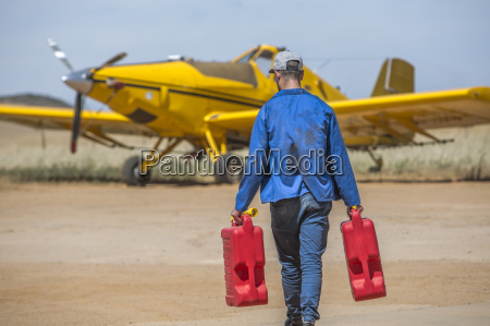 mechanic carrying jerry cans towards yellow