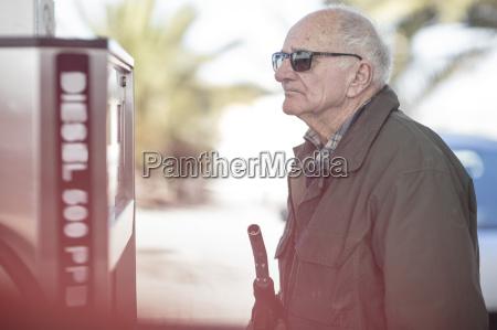 elderly man holding petrol pump at