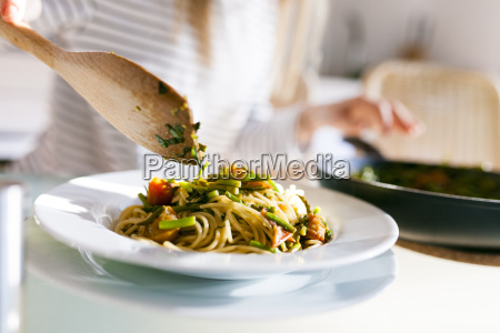 young woman serving vegan pasta dish