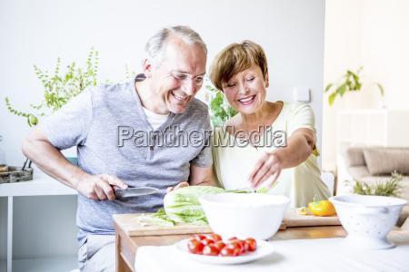 happy senior couple in kitchen preparing