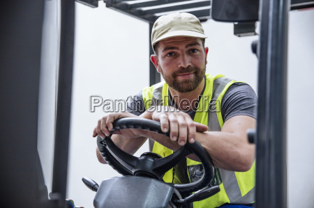 portrait of confident man on forklift