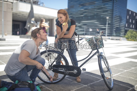 man helping woman inflating her bicycle