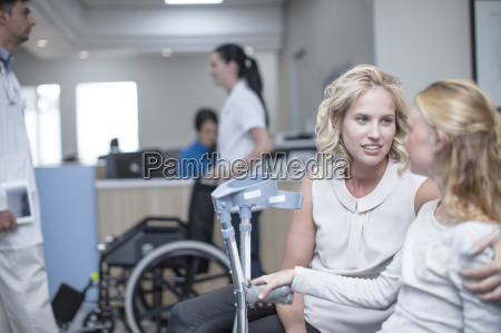 girl with crutches sitting with her