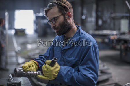 factory worker operating power tool