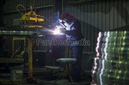 man welding steel in factory