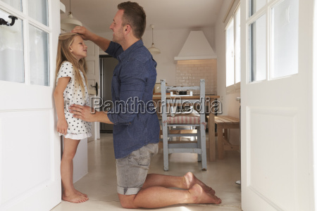 father measuring daughters height against wall