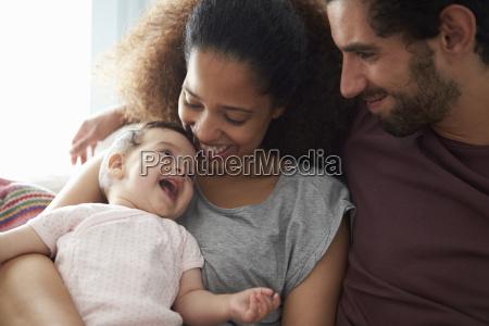 parents sitting on sofa cuddling baby