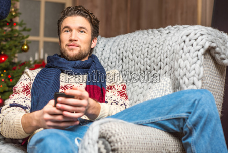 handsome man in sweater sitting in