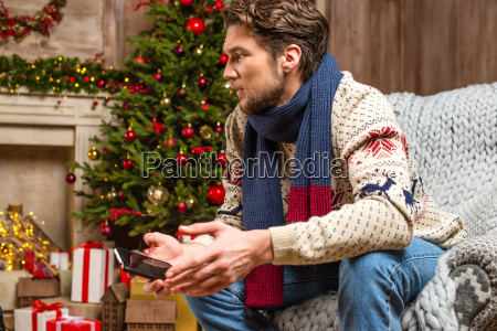 man in knitted sweater holding smartphone