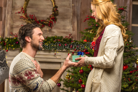 man presenting gift box to woman