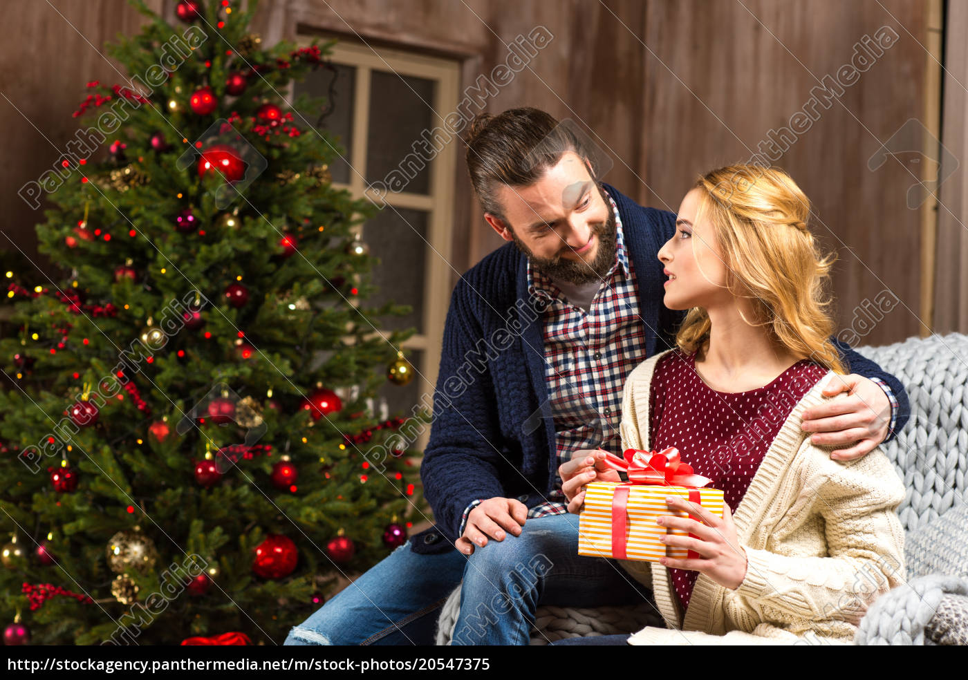 couple, sitting, with, christmas, present - 20547375