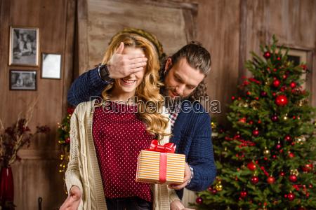man, giving, christmas, present, to, woman - 20547331