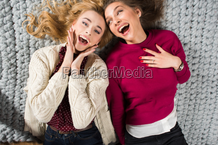 women lying on grey carpet