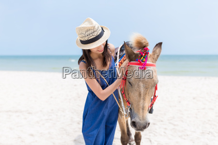 woman play with horse in sand
