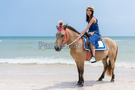 beautiful woman riding horse in sand
