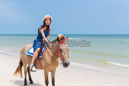 woman riding horse on beautiful sand