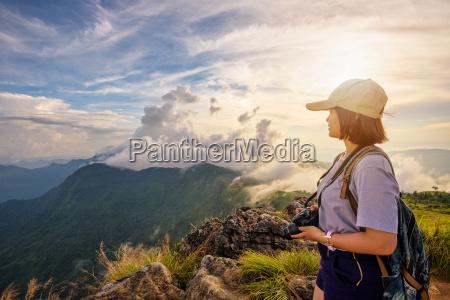 girl tourist on mountains at sunset