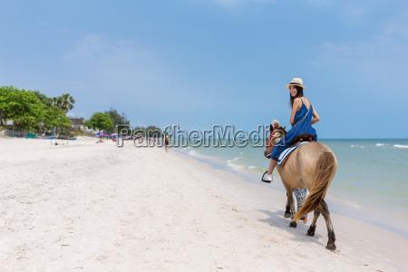 woman riding horse on sand beach